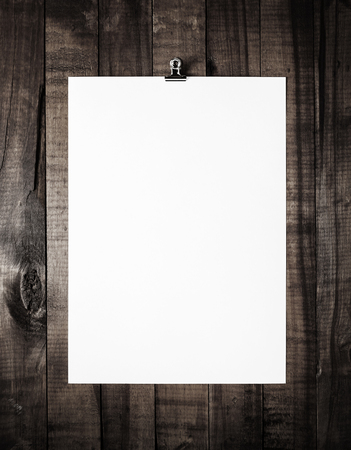 white poster: Blank letterhead on vintage wooden table background. White paper poster. Blank paperwork template. Overhead view.