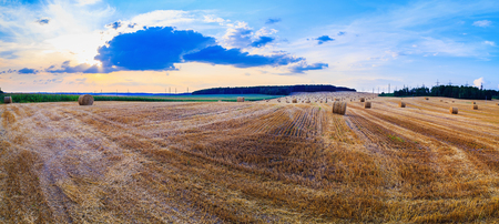 Field of cut grass with straw bales. Sunset sky with beautiful clouds. Autumn landscape in the countryside. Stock Photo