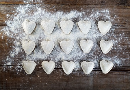 Heart shaped ravioli with flour, on vintage wood table background. Cooking dumplings. Top view. Stock Photo