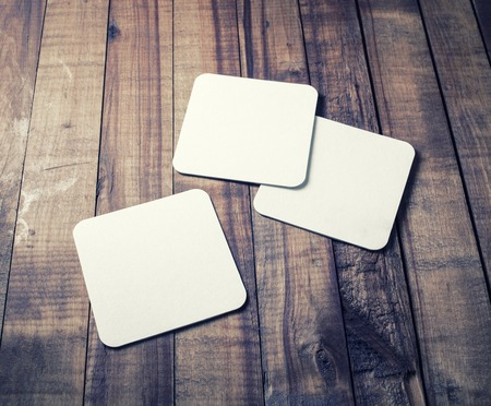 Photo of three blank beer coasters on vintage wood table background. Blank template for your design.