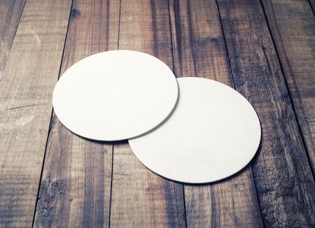 Two blank white beer coasters on vintage wooden table background. Responsive design mockup. Reklamní fotografie