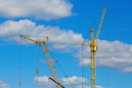 Yellow tower crane and mobile construction crane against blue sky background Stock Photo