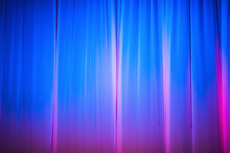 Bright blue stage curtain with spotlight. Abstract background.