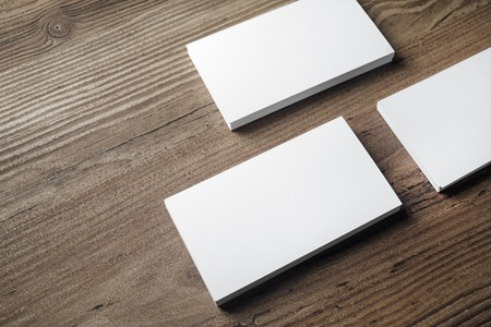 paper sheet: Blank white business cards on wood background. Mock-up for branding identity. Blank template for placing your design. ID mock up. Stock Photo