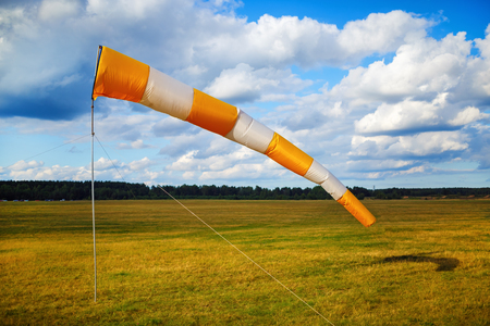 Windsock at small airfield. Blue sky with clouds and field of grass.