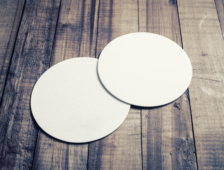 Two blank white beer coasters on vintage wooden table background. Banco de Imagens