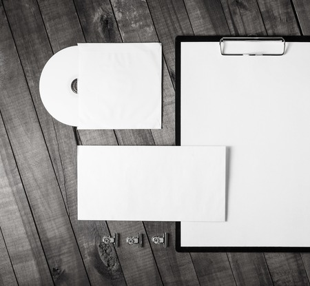 white sheet: Photo of blank corporate stationery set on wood table background. Top view.