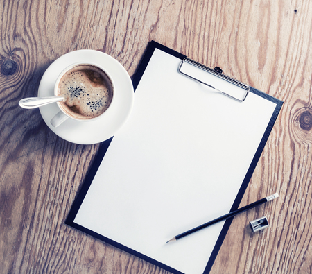 white sheet: Blank letterhead, clipboard, coffee cup, pencil and sharpener. ID template on wood table background. Mock up for placing your design. Top view. Stock Photo