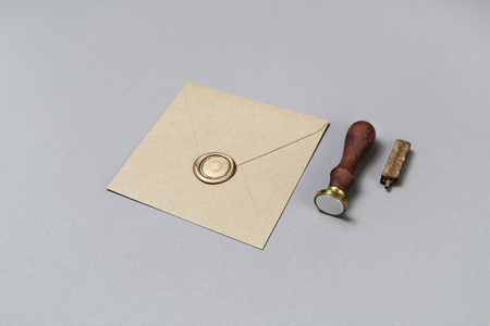 Craft paper envelope with wax seal and stamp on gray paper background.