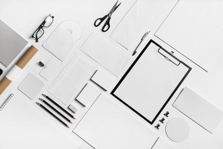 Fotografia pusty materiały ustawiający na białego papieru tle. Identyfikacja wizualna makiety do umieszczenia projektu. Płaskie leżało.