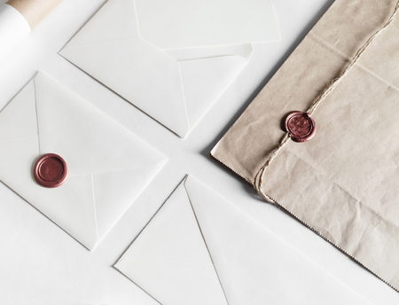 Envelopes and seal stamp on paper background. Vintage still life with postal accessories. Blank stationery. Responsive design mockup.