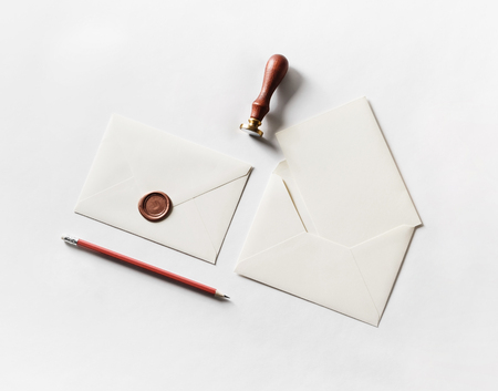 Envelope, seal, stamp and pencil on paper background. Responsive design mockup. Blank stationery. Top view.