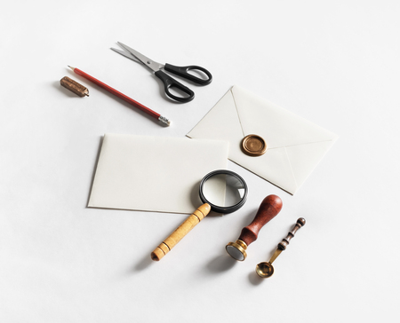 Blank vintage envelope and stationery on white paper background. Responsive design mock up. Top view.