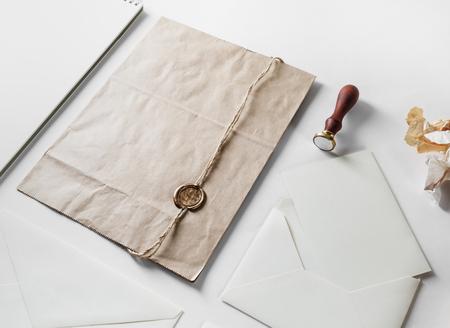 Vintage postal stationery with craft paper bag, wax seal, stamp and blank envelope on black paper background. Banque d'images