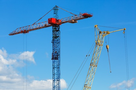 Two construction cranes. Tower crane and mobile construction crane against blue sky background. Stock Photo