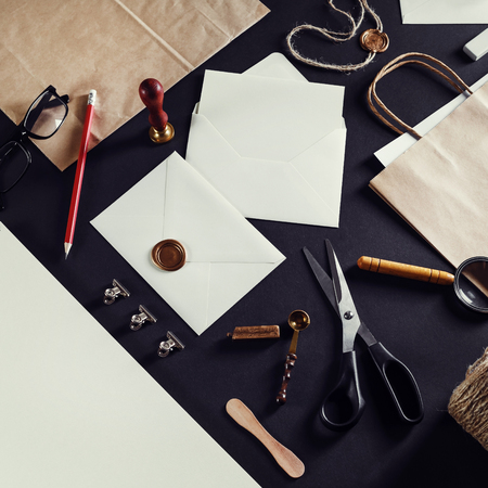 Photo of stationery set on black paper background. Vintage toned image. Top view. Flat lay.