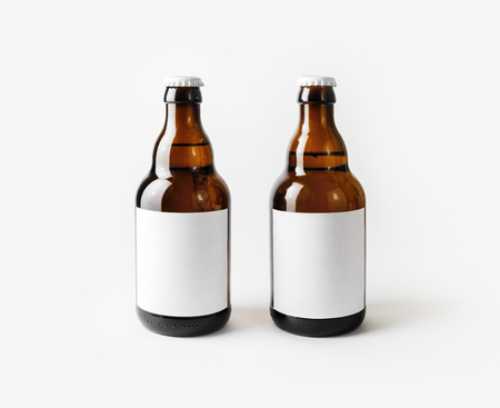 Two brown beer bottles with blank labels. Imagens