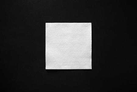 Blank white paper napkin on black background with copy space. Flat lay. Reklamní fotografie
