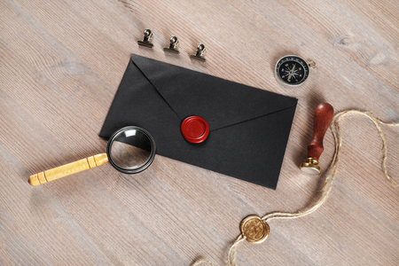 Blank black vintage envelope, sealing wax, magnifier, stamp, compass and stamp on wooden background. Responsive design mock up. Postal stationery. 免版税图像