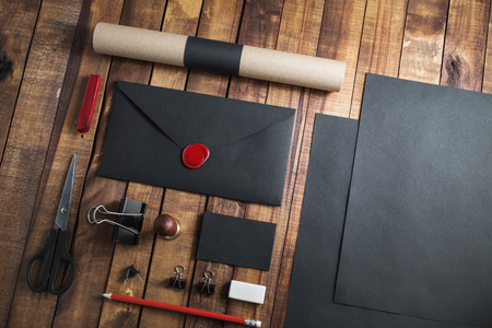 Photo of blank black stationery set on vintage wooden table background. Mock up for branding identity.