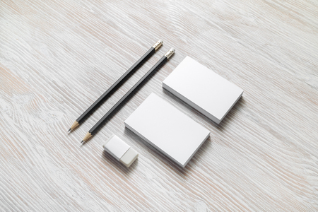 Blank corporate stationery set on light wood table background. Business cards, pencils and eraser. Imagens