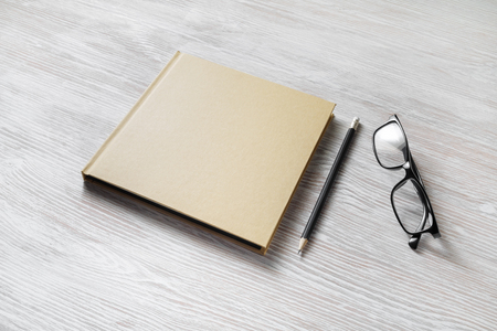 Photo of closed blank square book, glasses and pencil on wooden background. Template for placing your design.
