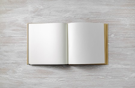 Blank book mock up on light wooden background. Flat lay.