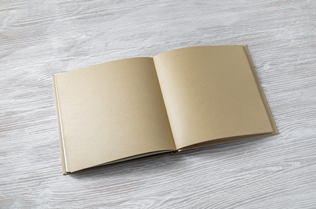 Open book with blank craft paper pages on light wooden background. 免版税图像