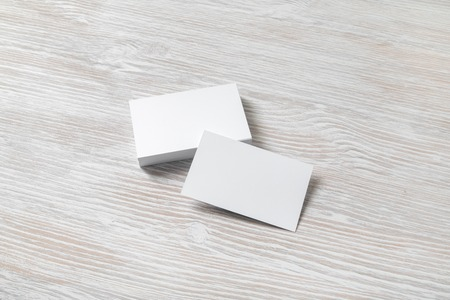 Blank white business cards on light wooden background. Mockup for branding identity. Template for graphic designers portfolios.