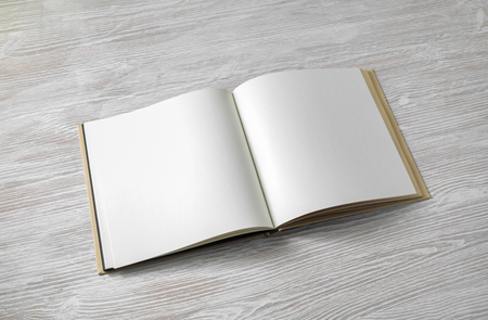 Opened blank square book on light wood table background.