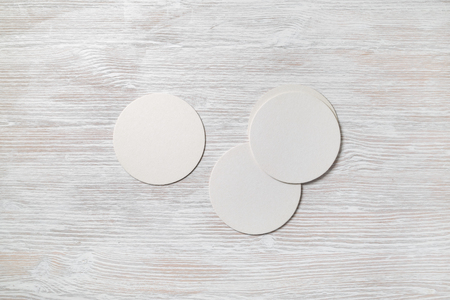 Photo of blank beer coasters on light wooden background. Template for placing your design. Top view. Flat lay. Stockfoto