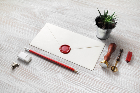 Blank paper envelope with red wax seal and stationery on light wooden background. Mockup for your design.