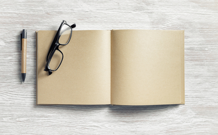 Photo of blank notepad with blank kraft paper pages, pen and glasses on light wood table background. Flat lay. Banque d'images - 124405986