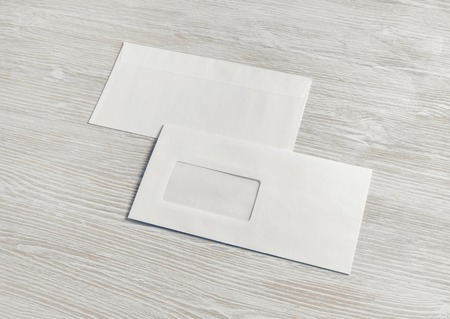 Sobres de papel en blanco sobre fondo de mesa de madera clara. Detrás y delante. Maqueta para colocar tu diseño.