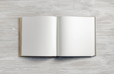 Opened blank square booklet on light wood table background. Flat lay.