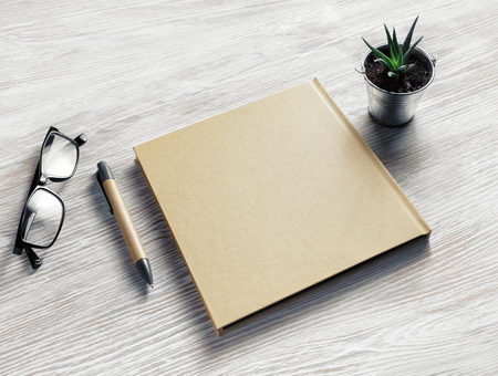 Photo of closed blank sketchbook, glasses, pen and plant on light wood table background. Blank stationery template. Banque d'images - 124406230
