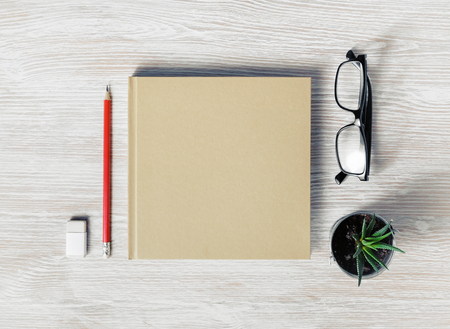 Photo of closed blank square booklet and stationery: glasses, pencil, eraser and plant on light wooden background. Template for placing your design. Flat lay. Banque d'images - 124406386