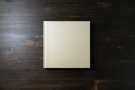 Blank square notebook or book on wooden background. Template for branding design. Flat lay.