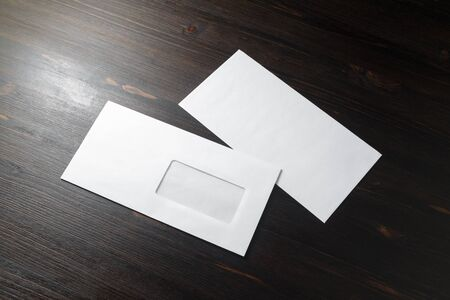 Two blank envelopes on wood table background. Front and back side. Template for branding identity.