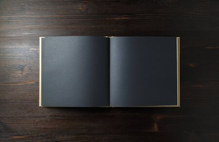 Opened blank black book on wooden background. Top view. Flat lay. Stock Photo