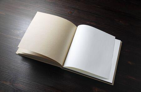 Libro en blanco abierto sobre fondo de mesa de madera. Plantilla para colocar tu diseño.