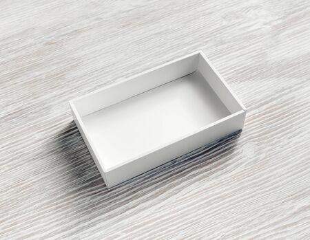 Blank white paper opened box on light wooden background. Reklamní fotografie