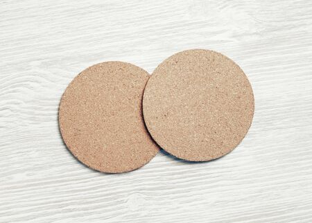 Photo of two cork beer coasters on light wood table background. Flat lay. Stockfoto