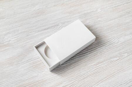 Blank opened box on light wood table background. Responsive design template. Reklamní fotografie