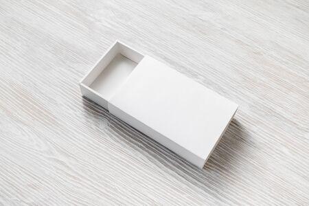 White cardboard box on light wooden background. Responsive design template.