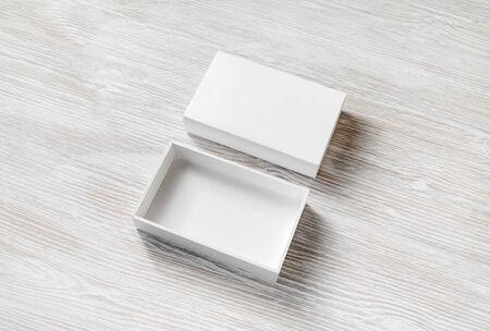 Blank white opened box on light wood table background. Reklamní fotografie
