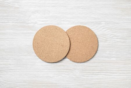 Two blank cork beer coasters on light wooden background. Responsive design template. Flat lay. Stockfoto