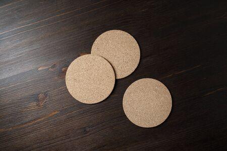 Three blank cork beer coasters on wooden background. Responsive design mockup. Flat lay. Stockfoto