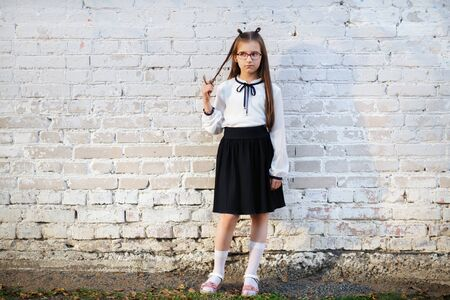 Schoolgirl standing against white brick wall background. Child girl in school uniform posing.