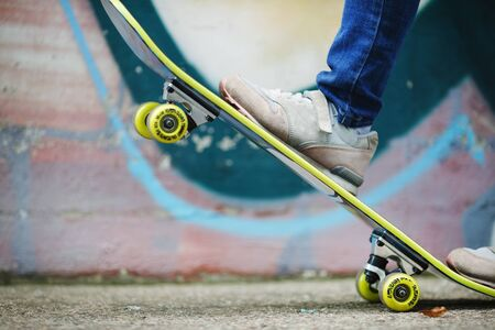 Skateboard stunt training. Skateboard and childrens feet in sneakers against wall background. Healthy lifestyle concept. Shallow depth of field. Selective focus.